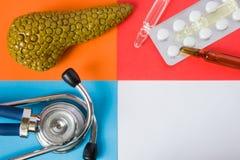 医疗或医疗保健设计观念照片器官胰腺、诊断医疗工具听诊器和疗程药片和通过 免版税库存图片