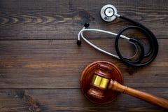 医疗法律,健康法律概念 惊堂木和听诊器在黑暗的木backgound顶视图复制空间 免版税库存照片