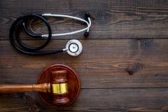 医疗法律,健康法律概念 惊堂木和听诊器在黑暗的木backgound顶视图复制空间 库存照片