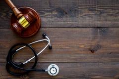 医疗法律,健康法律概念 惊堂木和听诊器在黑暗的木backgound顶视图复制空间 免版税库存图片