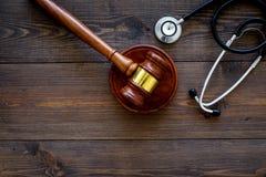 医疗法律,健康法律概念 惊堂木和听诊器在黑暗的木backgound顶视图复制空间 免版税图库摄影