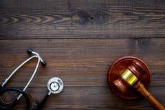 医疗法律,健康法律概念 惊堂木和听诊器在黑暗的木backgound顶视图复制空间 库存图片