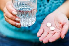 医疗药片和一杯水在妇女` s手上 库存照片