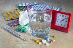 医疗药物、药片和水在一块玻璃在桌上 免版税库存图片