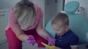 医疗面具的牙医和手套准备好对检查坐一点无忧无虑的男孩tooths与在椅子的镜子 影视素材