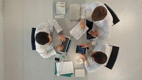 医院,医疗教育、医疗保健、人和医学概念-小组有片剂个人计算机计算机的愉快的医生 库存图片