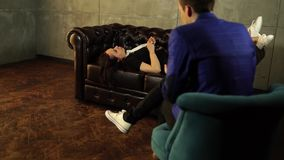 匿名的人的年轻女人回答的问题 年轻迷茫的妇女坐皮革长沙发和谈话与 股票录像