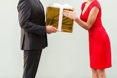 匿名者商人给红色礼服的一名当前妇女 免版税库存图片