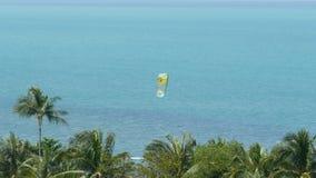 匿名kiteboarder在风平浪静 有风筝骑马委员会的遥远的人蓝色海水镇静表面上在热带的 股票视频