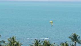 匿名kiteboarder在风平浪静 有风筝骑马委员会的遥远的人蓝色海水镇静表面上在热带的 股票录像