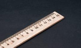 十五cm 一般尺寸 在黑背景的木统治者 简单的统治者 校务委员会背景 库存照片