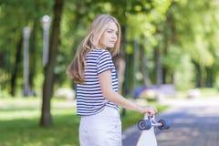 十几岁生活方式概念和想法 摆在与长的滑板的白肤金发的白种人十几岁的女孩在绿色森林里户外 免版税库存照片