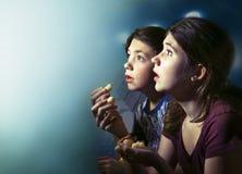 十几岁男孩和女孩观看的恐怖片影片 免版税库存照片