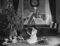 十几岁的女孩与圣诞树的阅读书(所有人被描述不更长生存,并且庄园不存在 供应商warranti 免版税库存照片