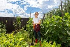 十几岁的女孩与铁锹一起使用在庭院 库存图片