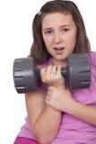 十几岁的女孩举的重量 免版税库存图片
