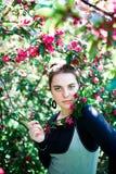年轻十几岁的女孩享用开花的树在晴朗的公园开花气味 春天秀丽没有过敏的 图库摄影