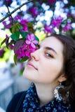 年轻十几岁的女孩享用开花的树在晴朗的公园开花气味 春天秀丽没有过敏的 免版税库存照片