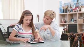 十几岁的女孩使用一种片剂,并且她的妈妈坐接近她 股票录像