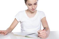 十几岁的女孩做着她的家庭作业 免版税库存图片