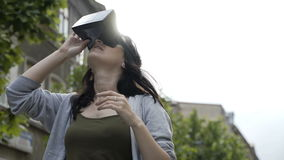 十几岁的女孩吃惊测试一个虚拟现实耳机使用Google室外 股票视频