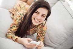 十几岁的女孩听的音乐通过手机 免版税库存图片