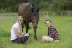 十几岁的女孩和她的母亲有她的小马的 图库摄影