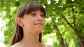 十几岁的女孩喝从秸杆的鸡尾酒,并且微笑在城市附近走 特写镜头 股票录像