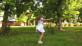 十几岁的女孩在一件白色圆点礼服转动并且在夏天公园微笑着 股票录像