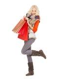 十几岁的女孩在冬天穿衣与购物袋 免版税库存照片