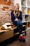十几岁的女孩在图书馆里 免版税库存图片