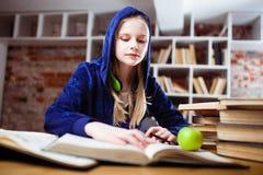十几岁的女孩在图书馆里 免版税图库摄影