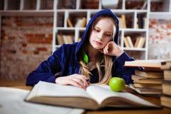 十几岁的女孩在图书馆里 免版税库存照片
