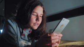 十几岁的女孩在她的智能手机在床上夜间看 聊天小青少年的敞篷的女孩在社会写一则消息 股票视频