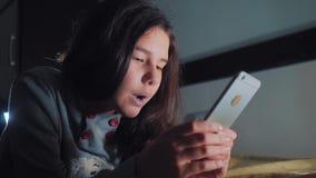 十几岁的女孩在她的智能手机在床上夜间看 聊天小青少年的敞篷的女孩在社会写一则消息 股票录像