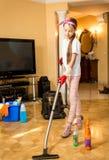 十几岁的女孩在客厅的清洁地板有吸尘器的 免版税库存照片
