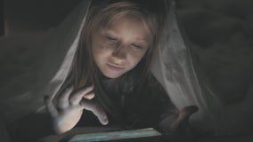 十几岁的女孩在播放一种片剂的床上在黑暗的光的社会互联网 关闭在的女孩观看的录影 影视素材