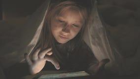 十几岁的女孩在播放一种片剂的床上在黑暗的光的社会互联网 关闭在的女孩观看的录影 股票录像