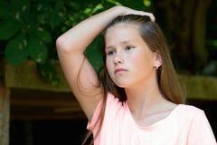 年轻十几岁的女孩在有哀痛表情的公园 免版税库存图片