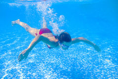 十几岁的女孩在游泳池潜水 图库摄影