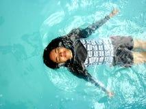 十几岁的女孩在水池的游泳仰泳 免版税图库摄影