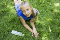 年轻十几岁的女孩在说谎在与瓶的绿草的公园  库存图片