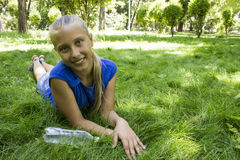 年轻十几岁的女孩在说谎在绿色草甸的公园 免版税图库摄影