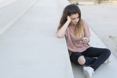十几岁的女孩坐与她流动看的一架梯子 库存图片