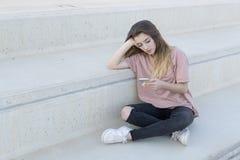 十几岁的女孩坐与她流动看的一架梯子 免版税图库摄影