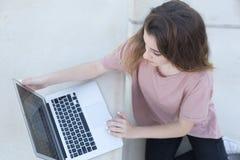 十几岁的女孩坐与她的膝上型计算机的一架梯子 免版税图库摄影