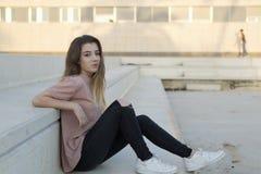 十几岁的女孩坐与沉思面孔的一架梯子 免版税图库摄影
