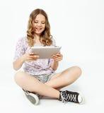 十几岁的女孩坐地板,拿着片剂 免版税图库摄影