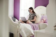 十几岁的女孩坐她的床使用便携式计算机 库存照片