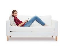 十几岁的女孩坐有片剂个人计算机的沙发 免版税库存照片